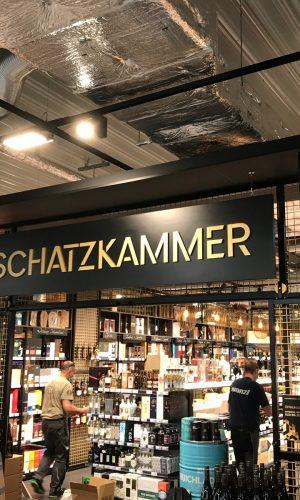 An Ketten montiertes Schild: Schatzkammer Schild im Edeka Markt. Hohlkammerplatte mit goldenen 3D-Buchstaben der Schreinerei Fleischmann