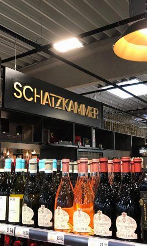 Direkt an die Wand montiertes Schild: Schatzkammer Schild im Edeka Markt. Hohlkammerplatte mit goldenen 3D-Buchstaben der Schreinerei Fleischmann
